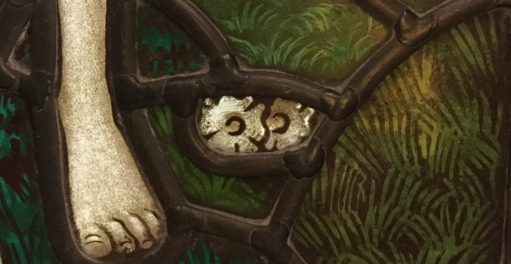 Detail of stained glass window, showing a foot and two white flowers, also visible as a cat's face