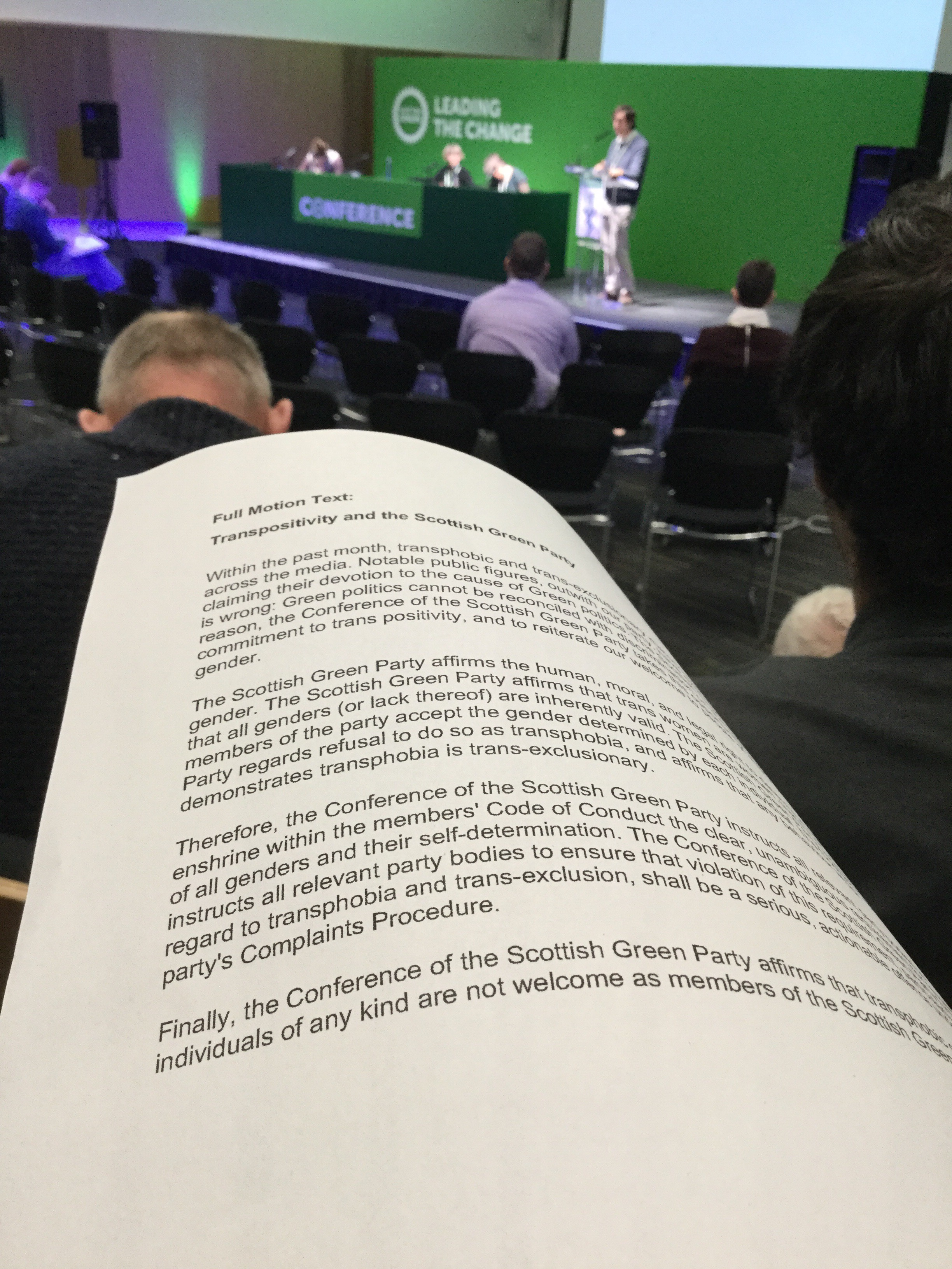 Text of the Scottish Green Party's trans-positivity motion, with the conference platform in the background