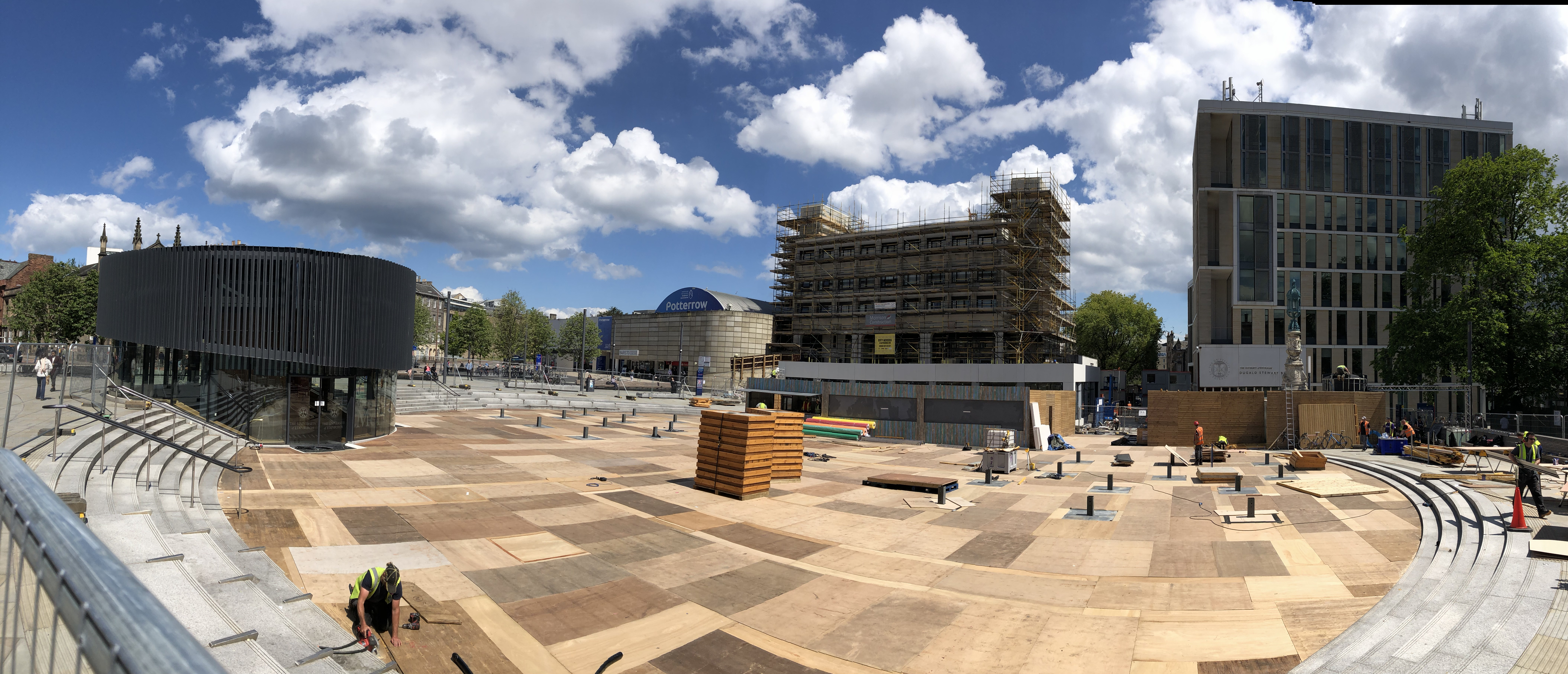 Bristo Square panorama on a sunny day, with wooden boarding being installed across the entire central area, along with small wooden buildings