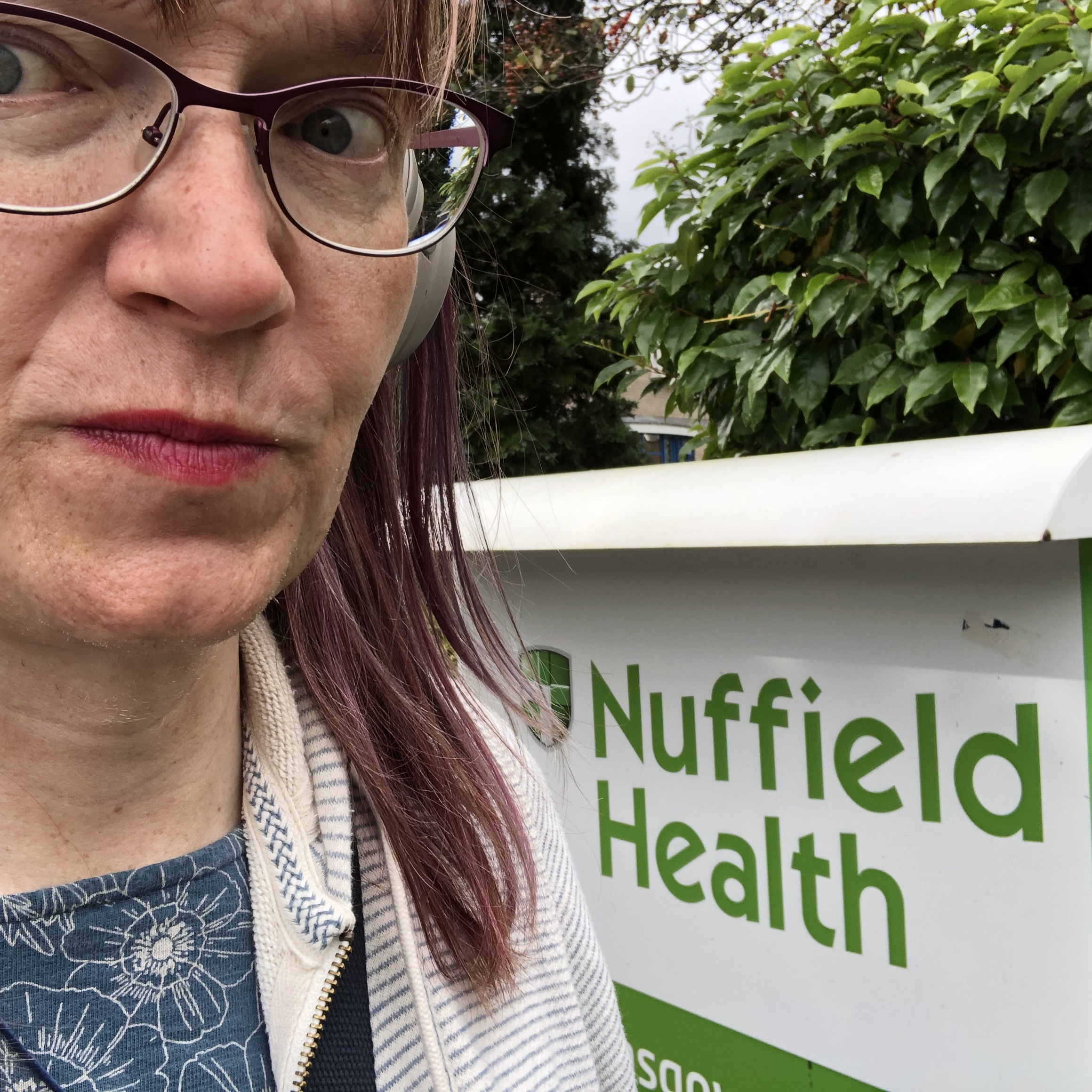 Anna standing pensively next to a sign reading 'Nuffield Health Glasgow Hospital'