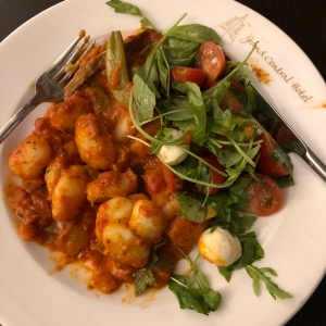 Gnocchi in a tomato sauce with mozzarella, tomato and basil salad on a Grand Central Hotel plate