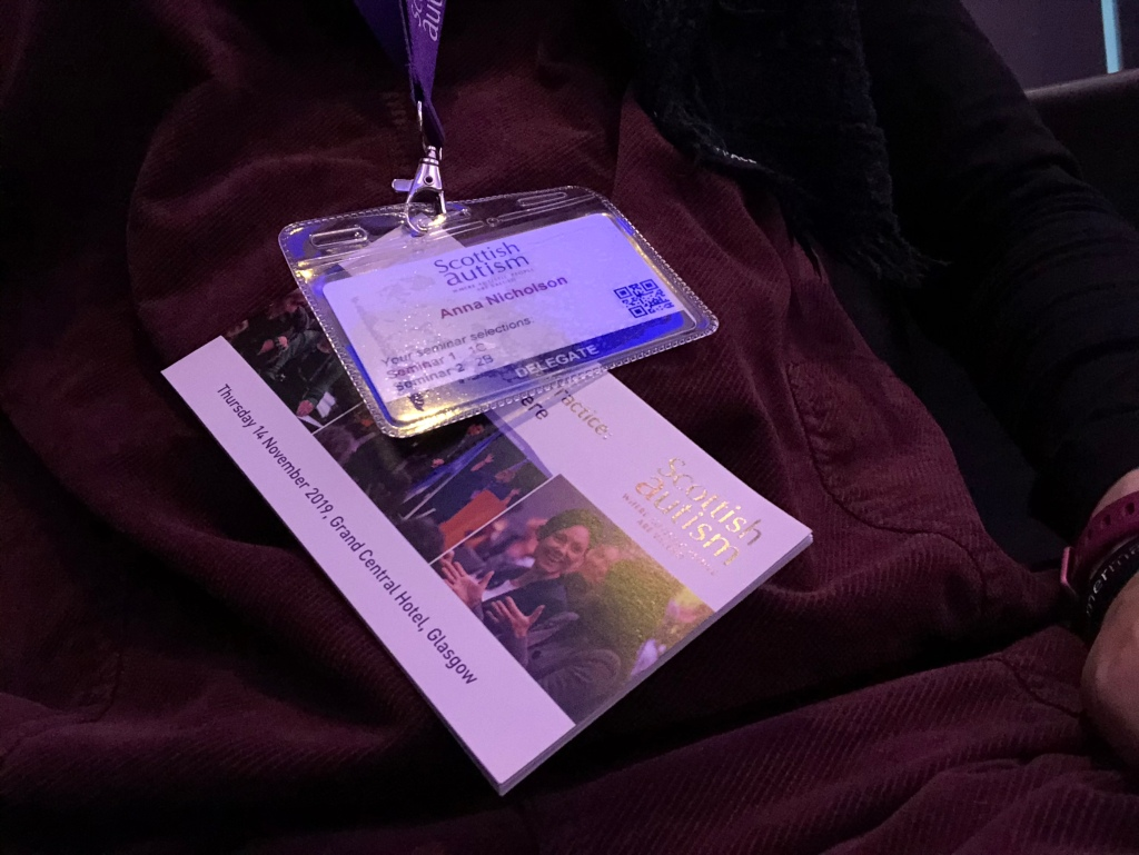 Anna's lanyard with her conference badge and a conference booklet attached
