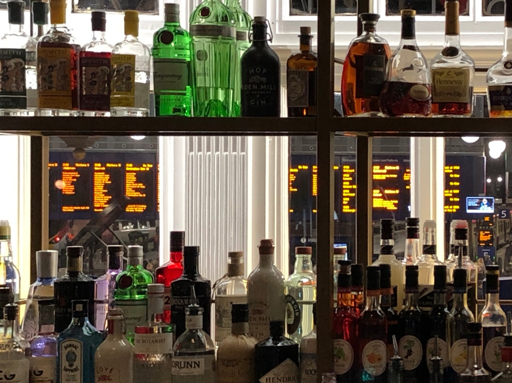 View through an assortment of bottles of spirits to the departure boards at Glasgow Central