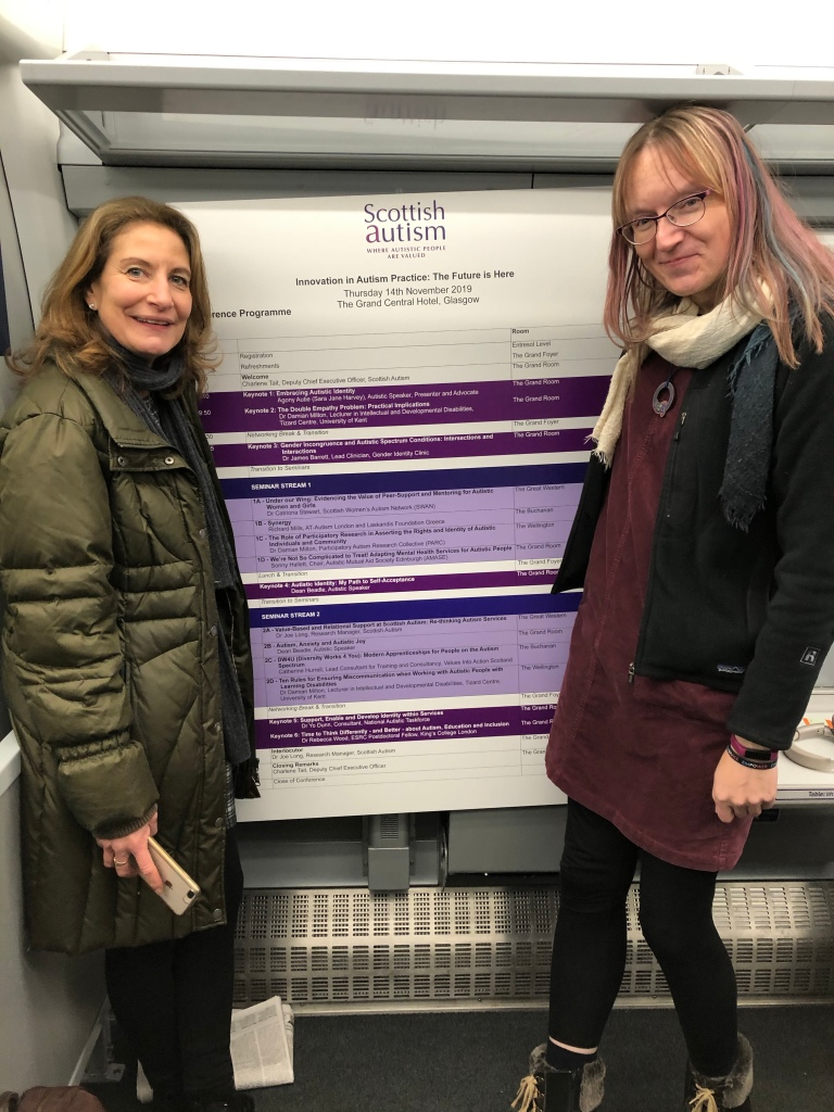 Fiona and Anna on a ScotRail train with a large (A0?) poster board with information about conference sessions