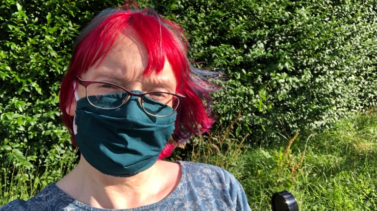 Anna sitting on a park bench during the summer. She is wearing a green face mask, and her hair is vibrant red and blue. There is a green hedge behind her.