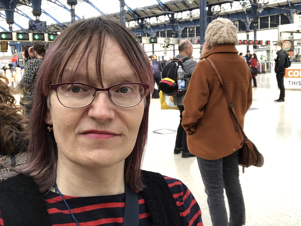 Photo of Anna at Brighton station, wearing a dark pinafore over a red and navy striped top. Her hair is shoulder length with magenta streaks. She is wearing lipstick and has little silver cat earrings. The station is clean and bright and quite busy.